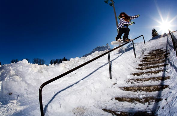 female pro snowboarding down a rail